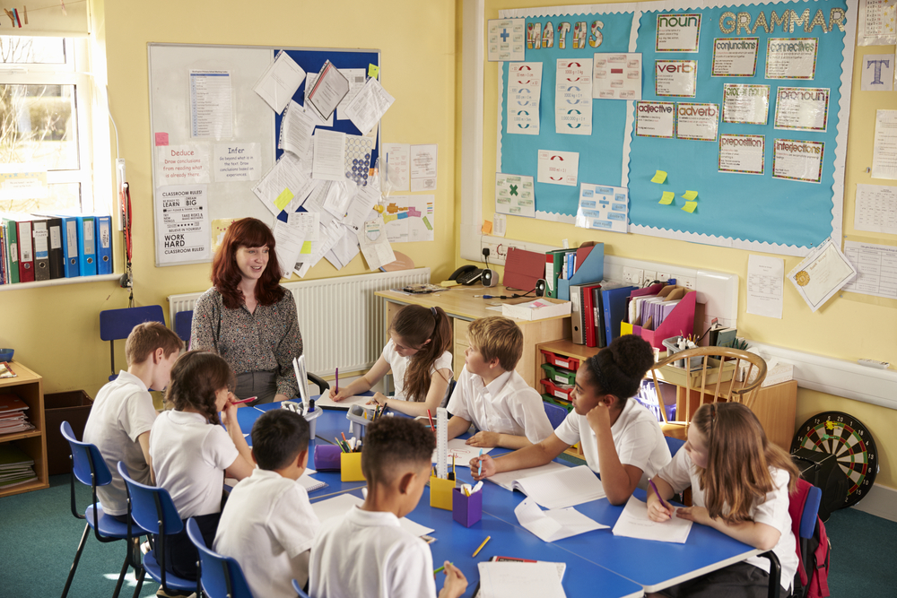 teacher teaching in a classroom full of students