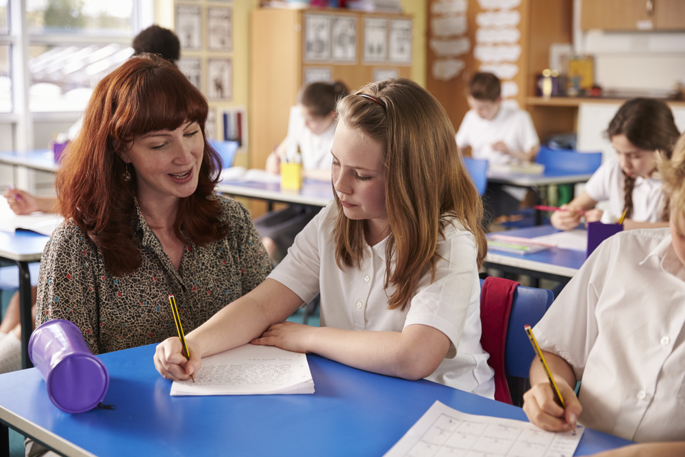 teacher teaching in a classroom helping a pupil at her desk