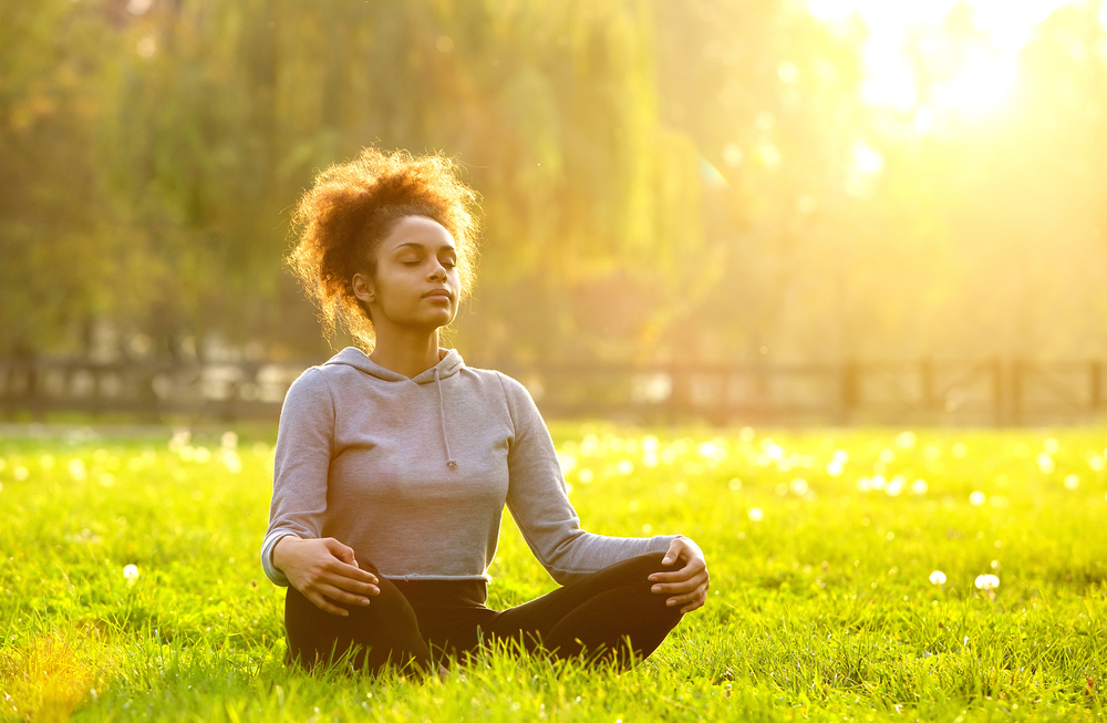 woman improving her mental health by meditating in nature