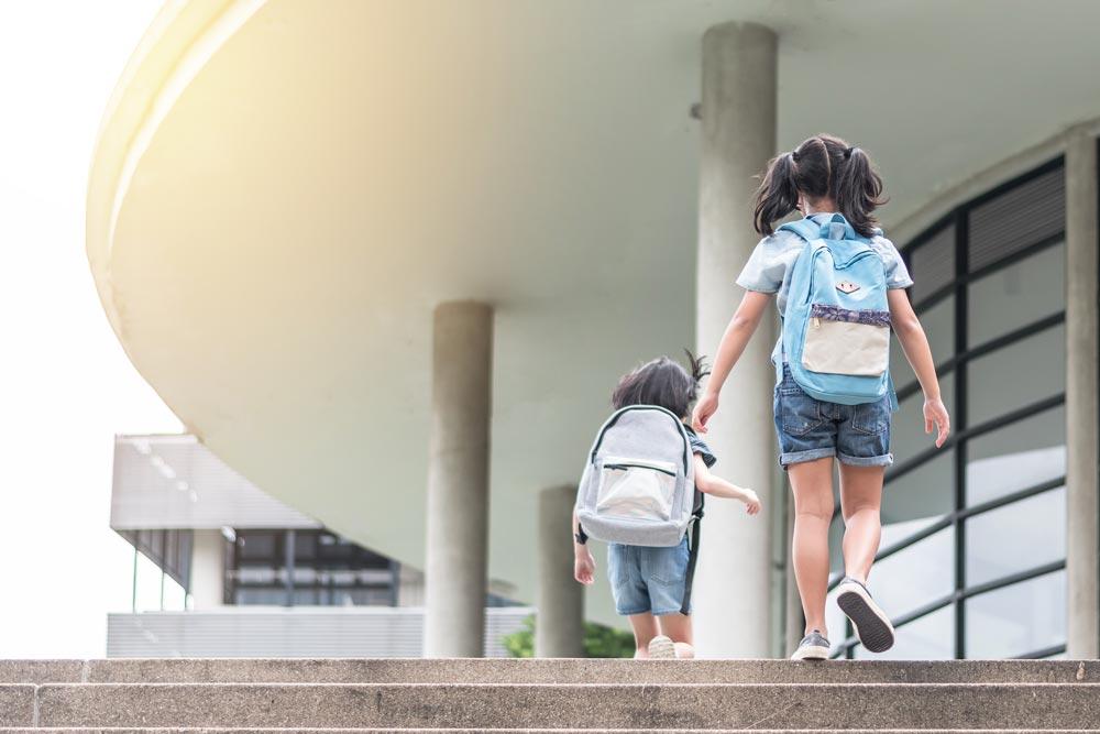kids with backpacks walking up school steps